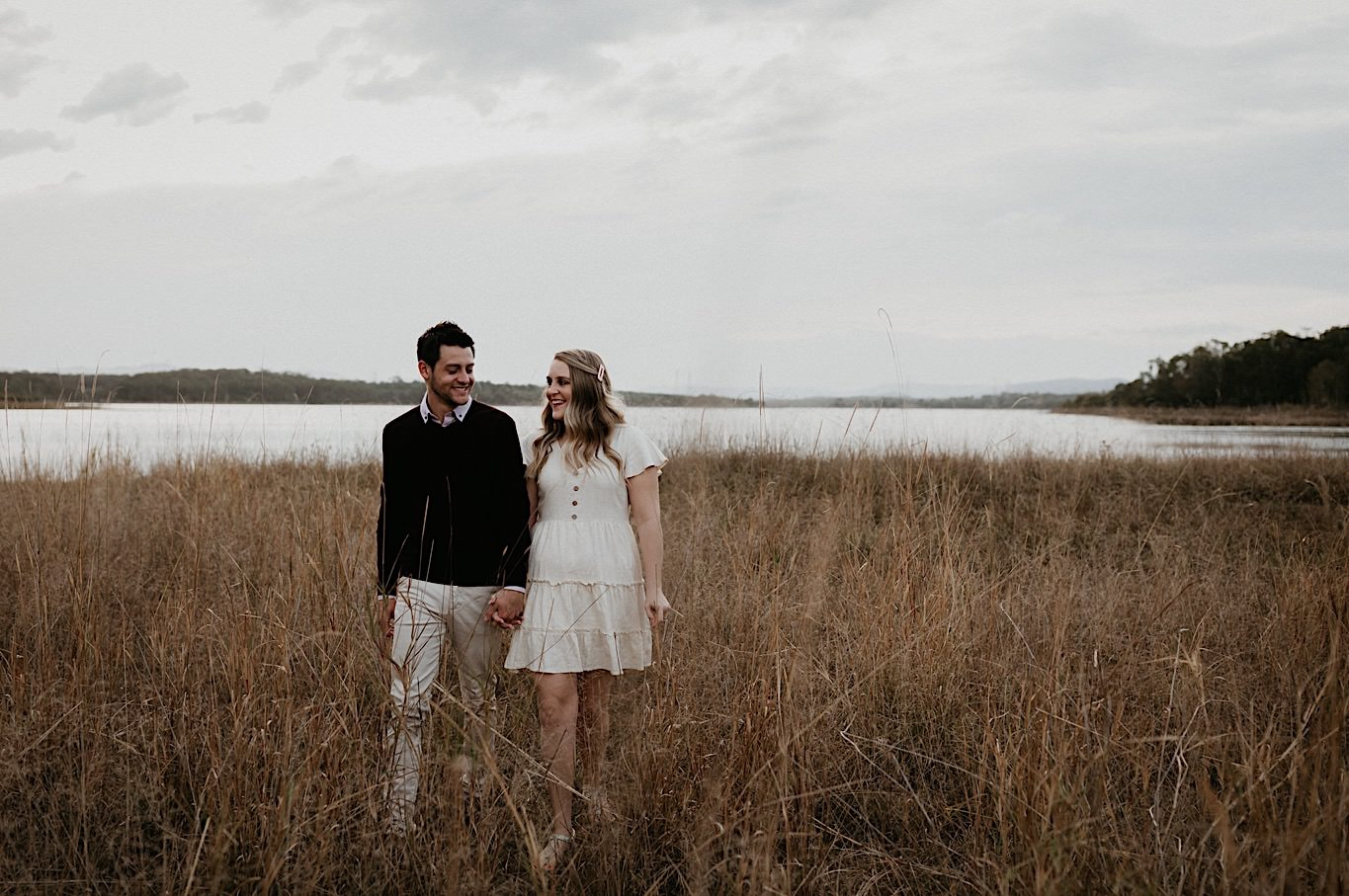 Romantic Sunshine Caost Engagement shoot in a grass field and with bougainvillea and sunset
